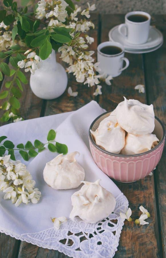 Biscotti e tazza di caffè delle meringhe Gocce casalinghe di baci di meringa con i fiori dell'acacia Foto dell'annata Copi lo spa fotografia stock libera da diritti