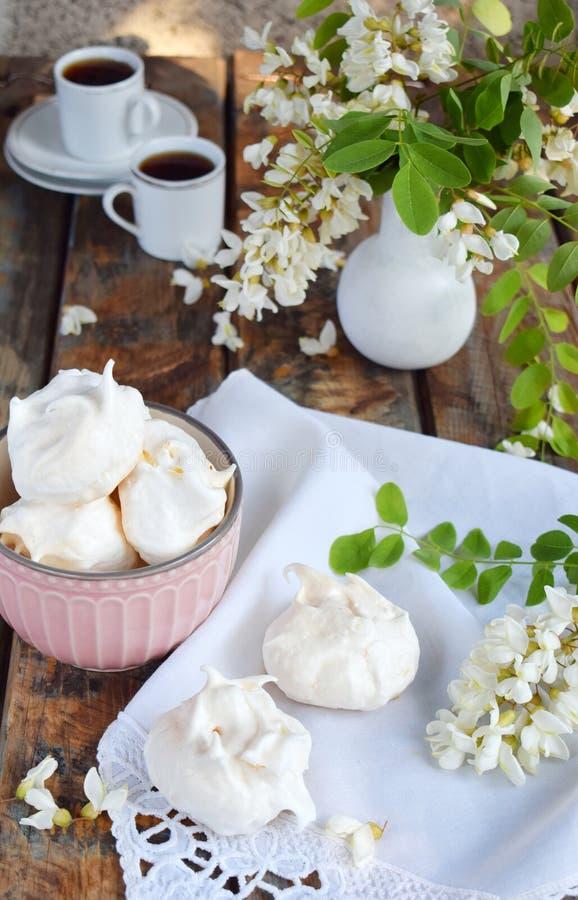 Biscotti e tazza di caffè delle meringhe Gocce casalinghe di baci di meringa con i fiori dell'acacia Foto dell'annata Copi lo spa fotografie stock libere da diritti