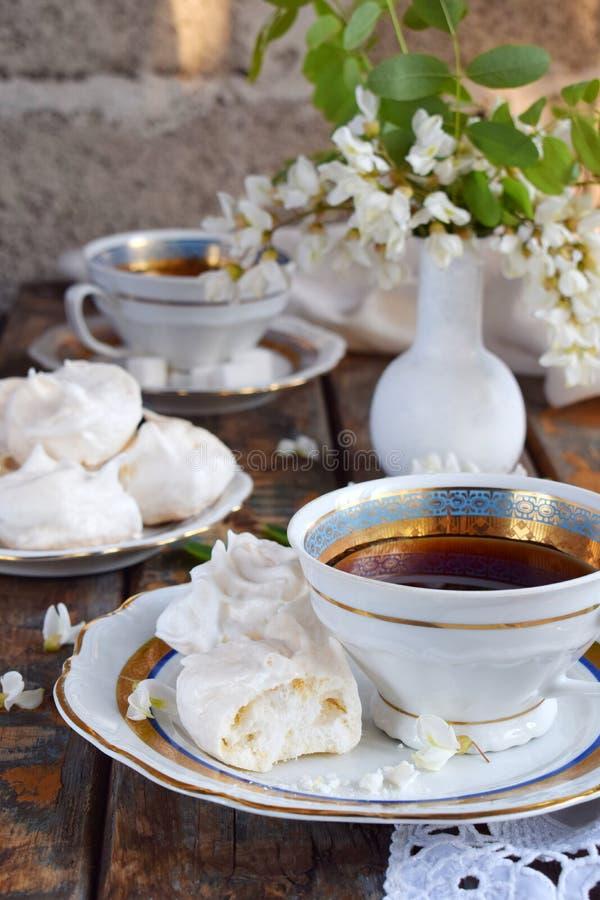 Biscotti e tazza di caffè delle meringhe Gocce casalinghe di baci di meringa con i fiori dell'acacia Foto dell'annata Copi lo spa immagine stock