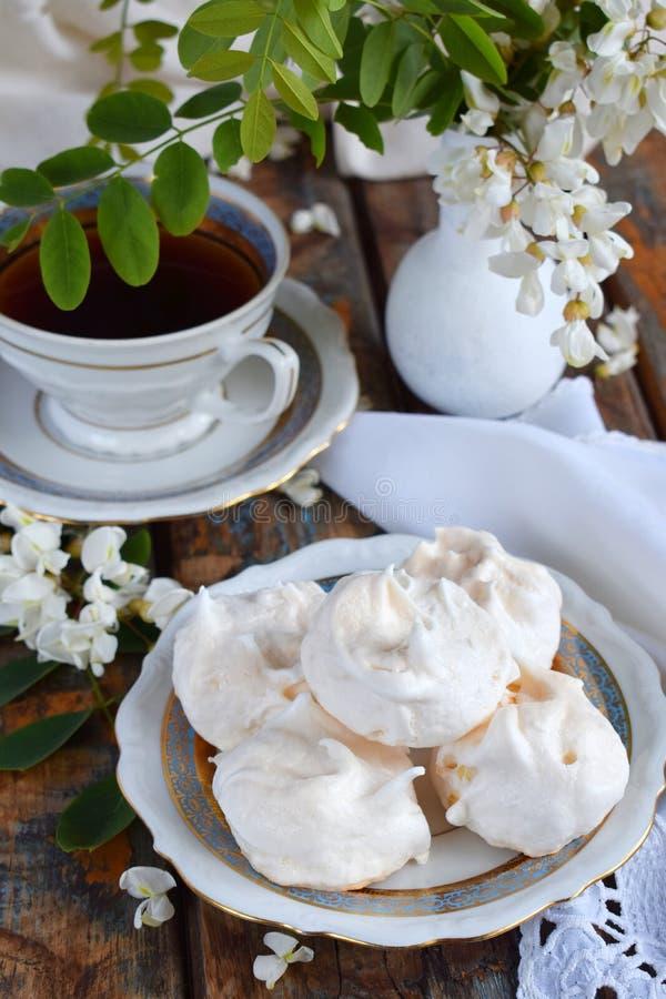 Biscotti e tazza di caffè delle meringhe Gocce casalinghe di baci di meringa con i fiori dell'acacia Foto dell'annata Copi lo spa fotografia stock
