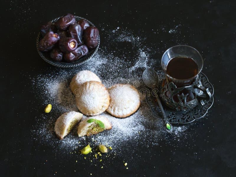 """Biscotti egiziani """"EL Eid di Kahk """"con le date servite in una tavola nera Biscotti della festivit? islamica di EL Fitr immagine stock"""
