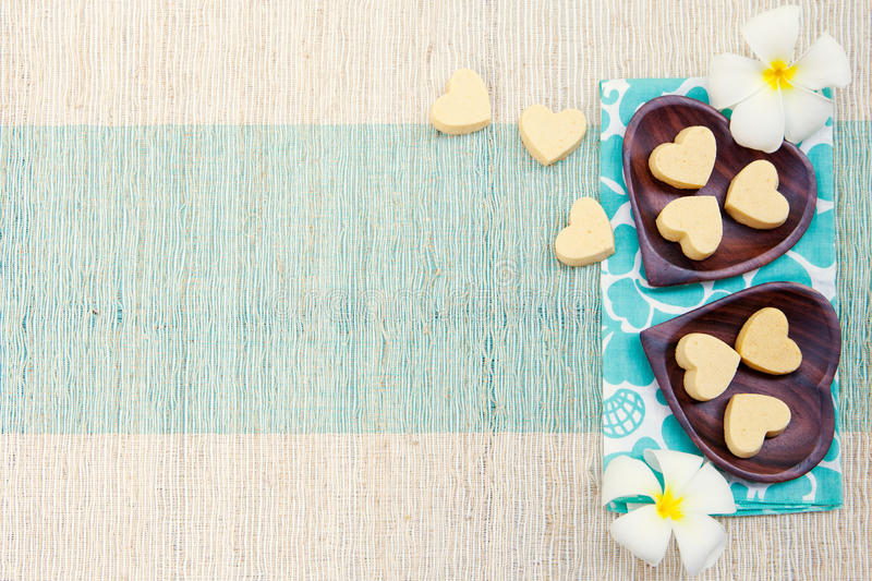 Biscotti fatti a mano di forma del cuore sulla vista superiore del fondo all'aperto blu del tovagliolo e del piatto di legno fotografia stock