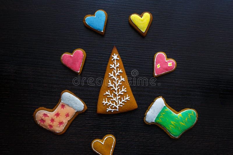 Biscotti festivi fatti a mano del pan di zenzero sotto forma di stelle, fiocchi di neve, la gente, calzini, personale, guanti, al immagini stock libere da diritti