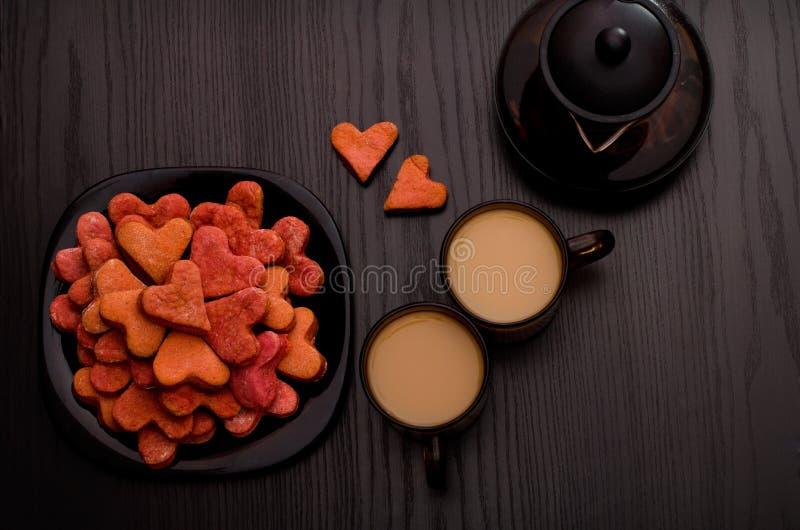 Biscotti in forma di cuore rossi, due tazze di tè al latte e teiera Giorno del biglietto di S fotografia stock libera da diritti