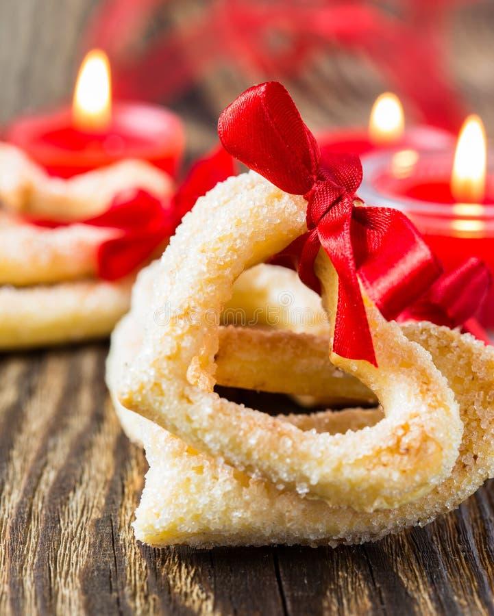 Biscotti a forma di del cuore con il nastro rosso immagini stock