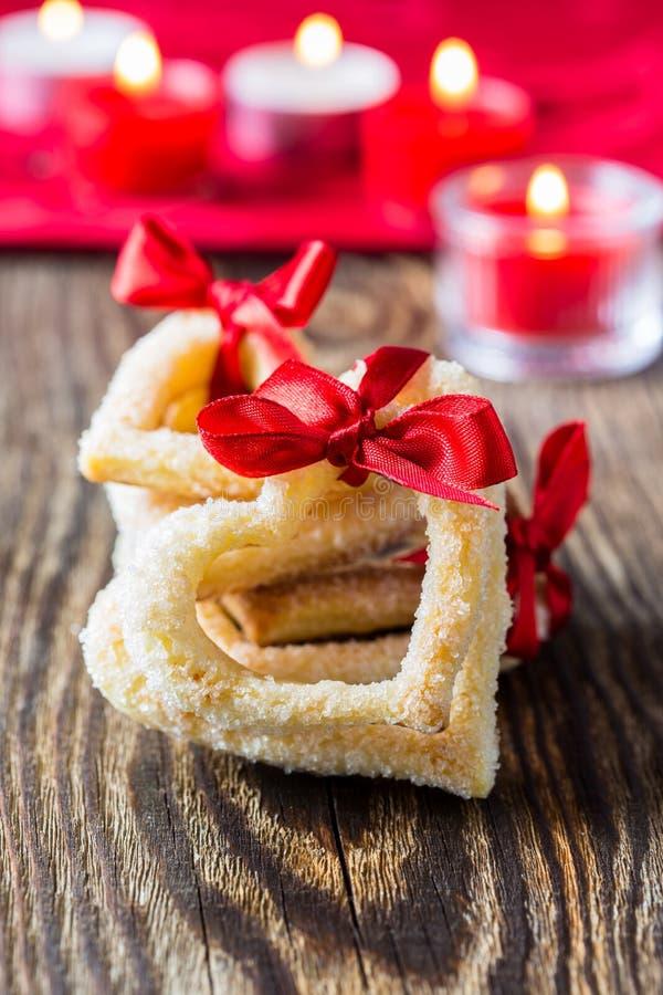 Biscotti a forma di del cuore con il nastro rosso fotografia stock