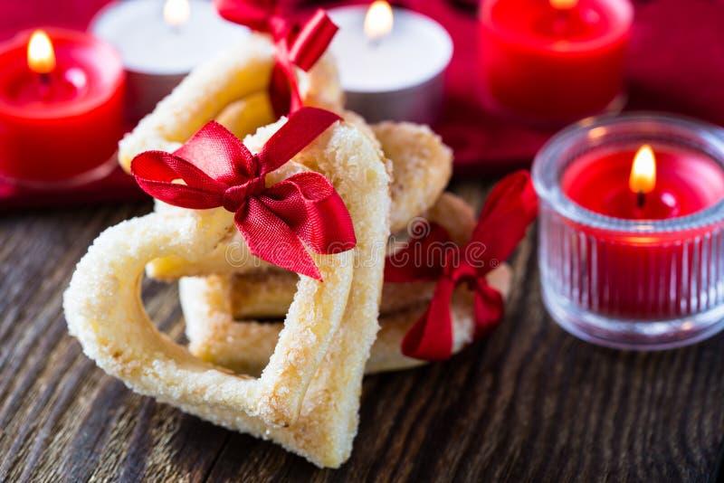 Biscotti a forma di del cuore con il nastro rosso fotografia stock libera da diritti