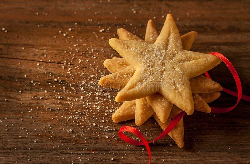 Biscotti a forma di stella di natale e nastro rosso su legno d'annata fotografia stock libera da diritti