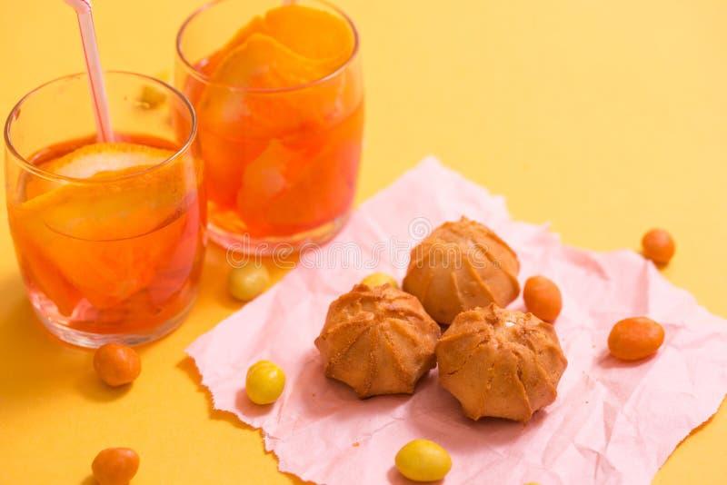 biscotti gialli, aranciata con i pezzi di frutta in una tazza di vetro su un fondo giallo Il concetto di estate immagini stock