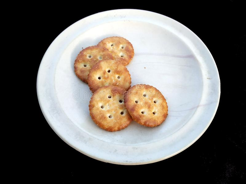 Biscotti in piatto bianco isolato su fondo nero fotografie stock