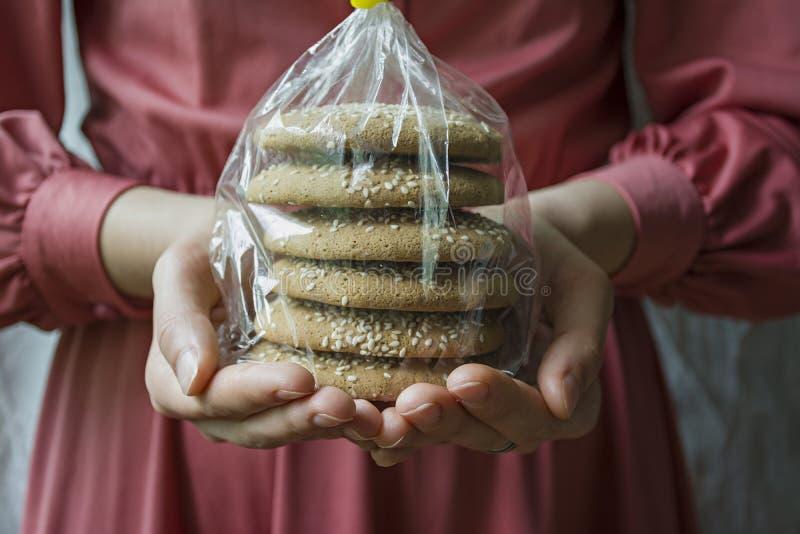 Biscotti saporiti Una ragazza sta tenendo un pacchetto con i biscotti di farina d'avena Vista frontale del primo piano fotografie stock libere da diritti