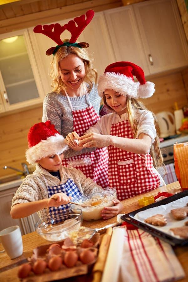 Biscotti sorridenti di Natale di cottura della madre e dei bambini a casa fotografia stock libera da diritti