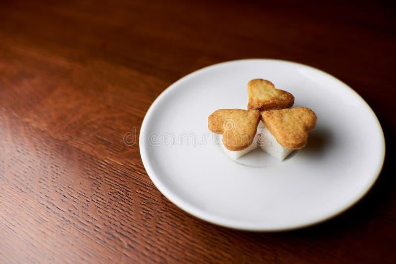 Biscotti sotto forma dei cuori che si trovano su un piattino fotografie stock libere da diritti