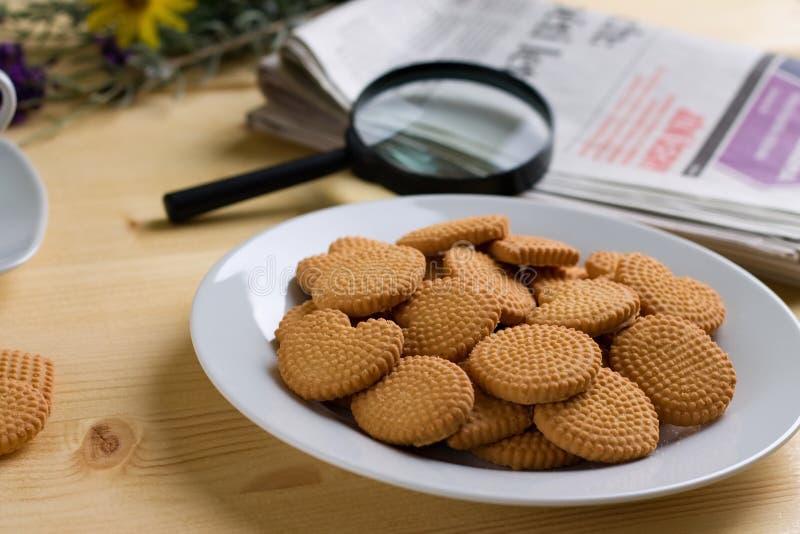 Biscotti sul piatto e sui giornali bianchi sulla tavola di legno fotografia stock