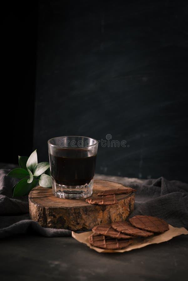 Biscotti tazza di caffè e di pepita di cioccolato di vetro sulla tavola fotografia stock libera da diritti