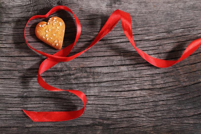 Biscotti uno e nastro rosso a forma di del cuore fotografie stock libere da diritti