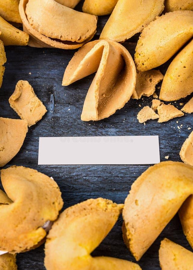 Biscotto di fortuna aperto incrinato con spazio su fondo di legno blu fotografia stock
