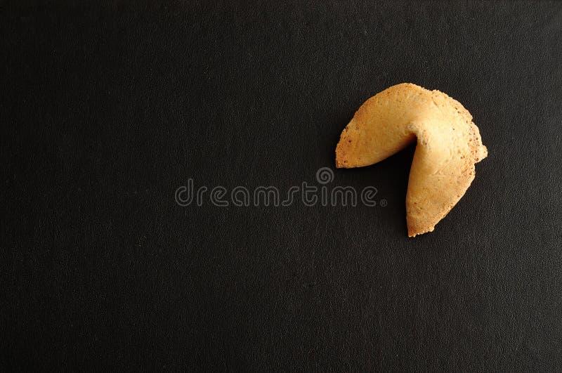 Biscotto di fortuna su un fondo nero immagini stock libere da diritti
