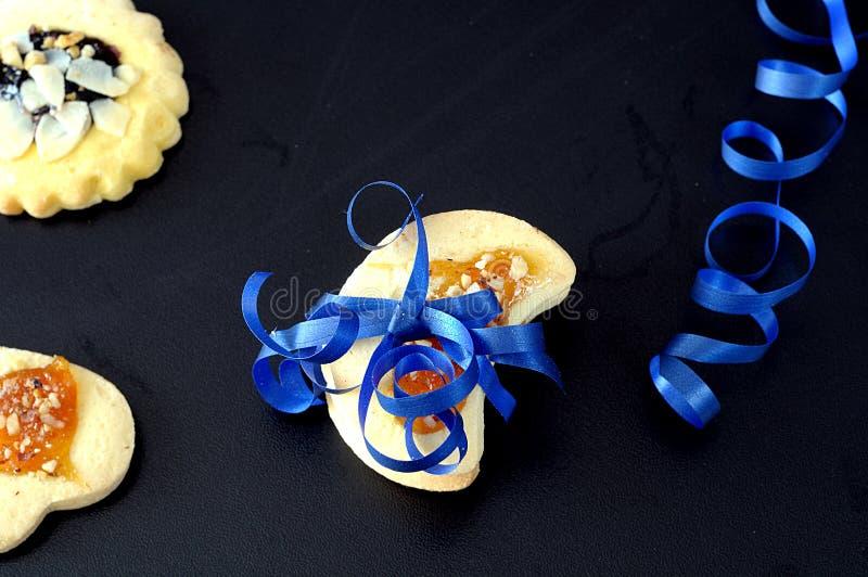 Biscuit attaché avec le ruban bleu sur le noir photo libre de droits