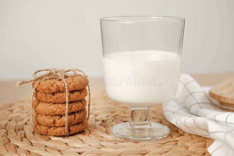 Biscuit avec un verre de support de lait sur un plateau en bois sur la table photo libre de droits