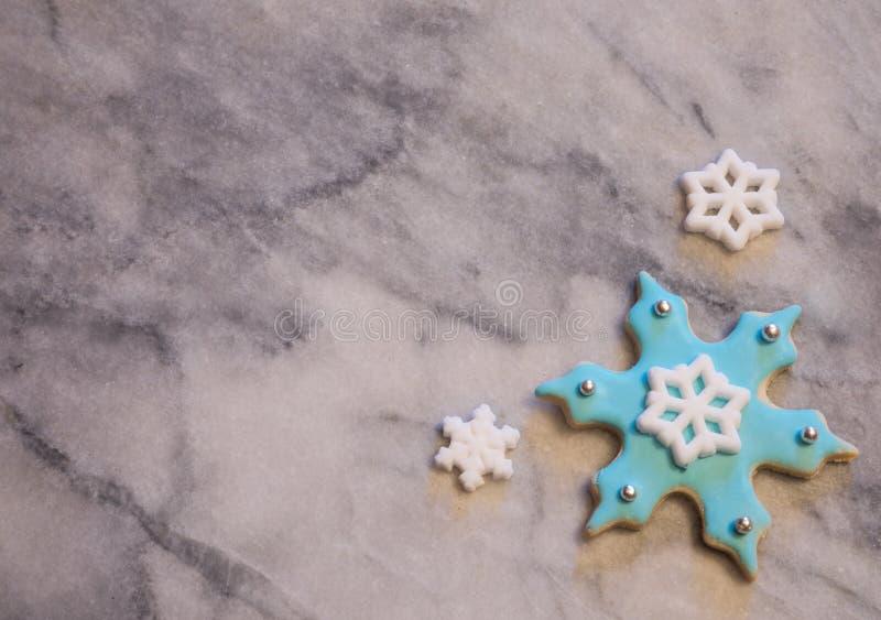 Biscuit bleu-clair de flocon de neige sur le fond de marbre gris et blanc image libre de droits