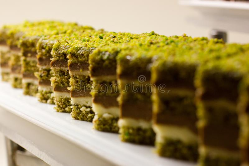 Biscuit cake with chocolate and pistachio crumbs stock photos