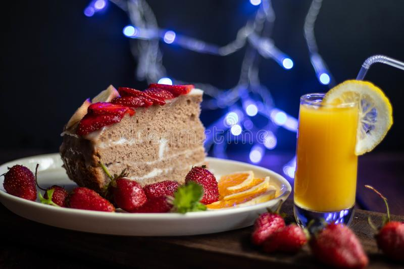 Biscuit cake with sour cream decorated with strawberries, fresh berry on a tray, with blue lights in the background, royalty free stock photo