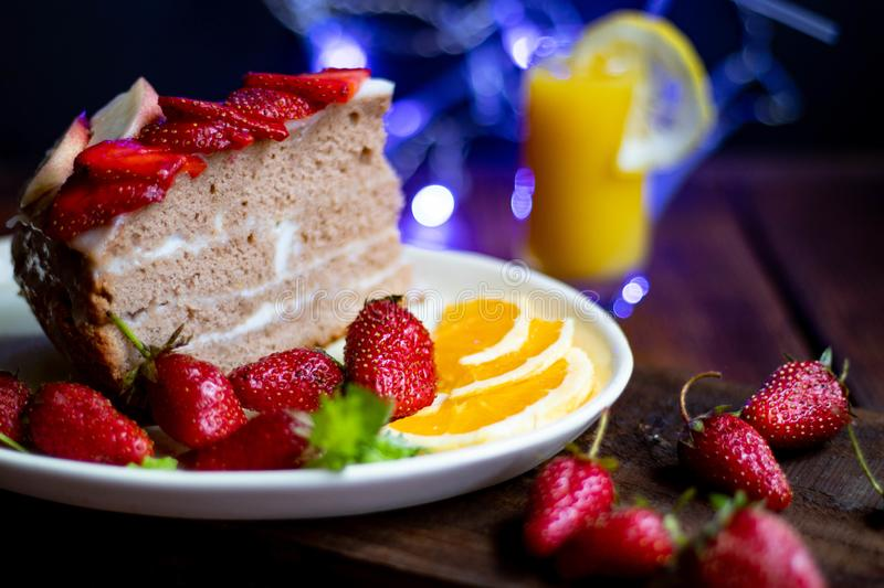 Biscuit cake with sour cream decorated with strawberries, fresh berry on a tray, with blue lights in the background, royalty free stock image