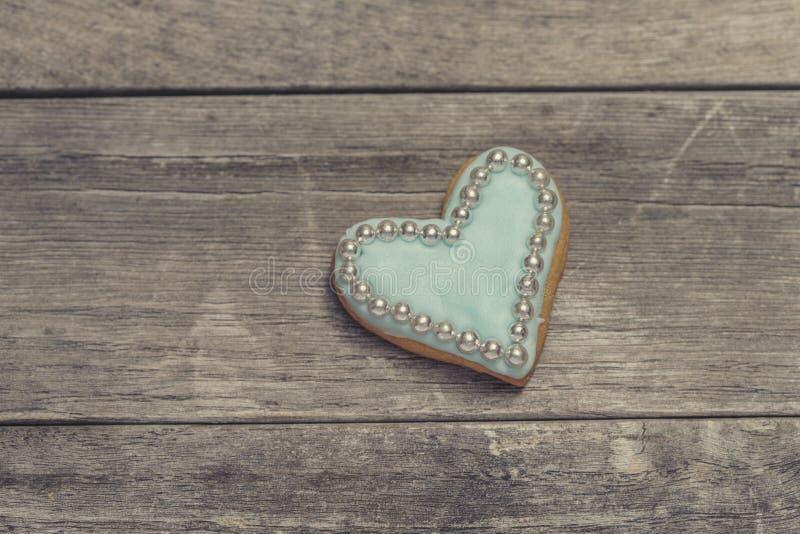 Biscuit de coeur couvert de glaçage bleu et de perles comestibles de perle images stock