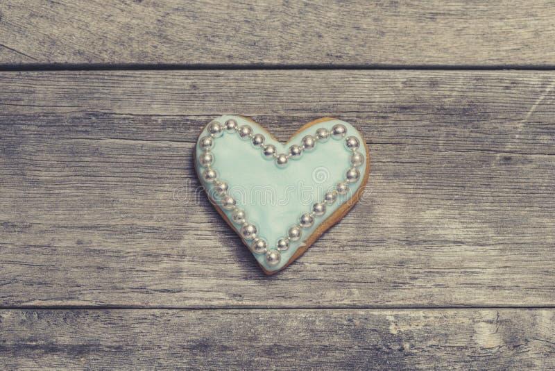 Biscuit de coeur couvert de glaçage bleu et de perles comestibles de perle photos stock