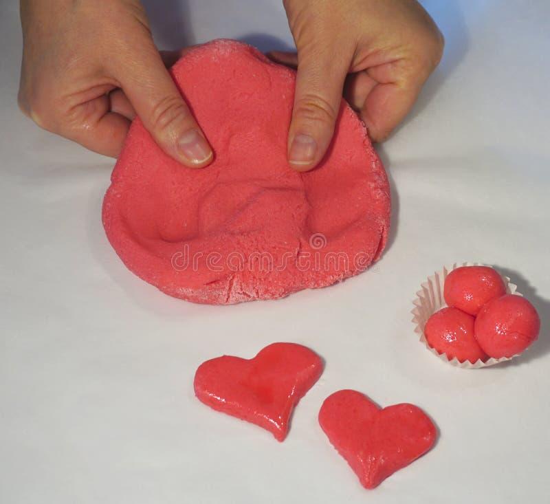 Biscuit de coeur fait de pâte avec des mains de femme photographie stock