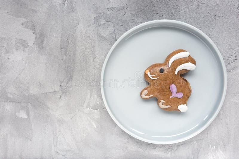 Biscuit de lapin de P?ques de pain d'?pice d'un plat sur un fond gris Concept de P?ques photo stock