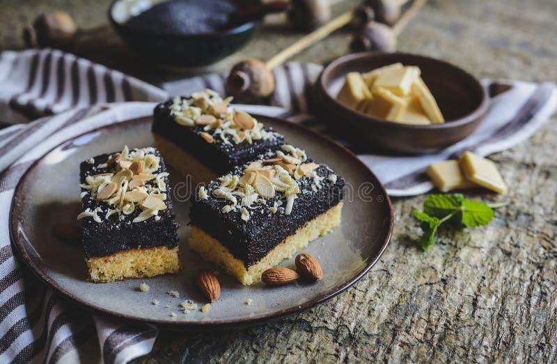 Biscuitgebak met de laag van het papaverzaad, met witte chocoladekrullen en gesneden amandel wordt verfraaid die royalty-vrije stock foto