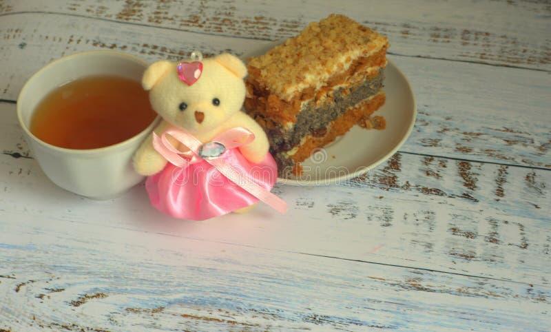 Biscuitgebak met papaverzaden op een plaat, een kop thee en een teddybeer die op een houten lijst liggen royalty-vrije stock afbeelding