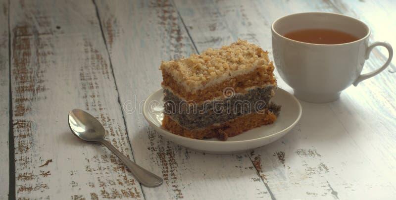 Biscuitgebak met papaverzaden op een plaat, een lepel en een kop thee op een houten lijst stock afbeelding