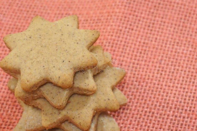 Biscuits épicés en forme d'étoile de Noël sur le fond rose de jute photographie stock