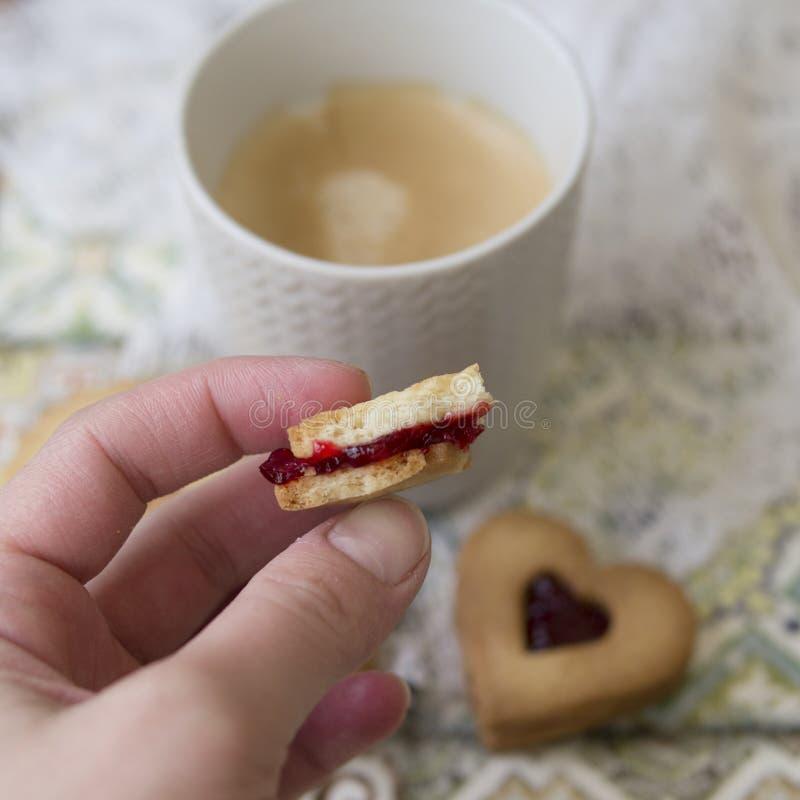 Biscuits avec de la confiture de canneberge sur un fond multicolore avec la serviette de dentelle Biscuits pour la Saint-Valentin image libre de droits
