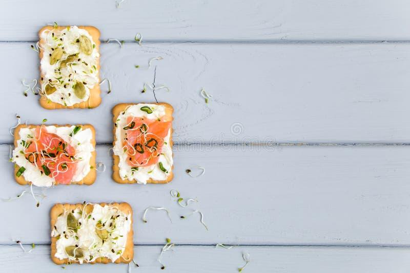 Biscuits avec le fromage fondu, les saumons, les graines et les verts Apéritifs de plat sur la table grise Casse-croûte sains, vu photos libres de droits