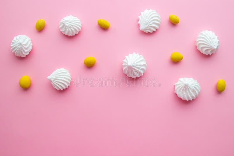Biscuits blancs de meringue avec les dragées jaunes sur le fond rose en pastel images stock