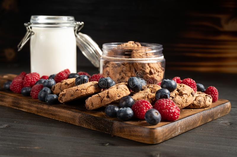 Biscuits, blueberries and strawberries in the spotlight stock image