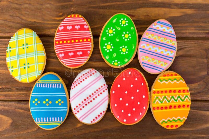 Biscuits colorés de Pâques sur le fond en bois brun images stock