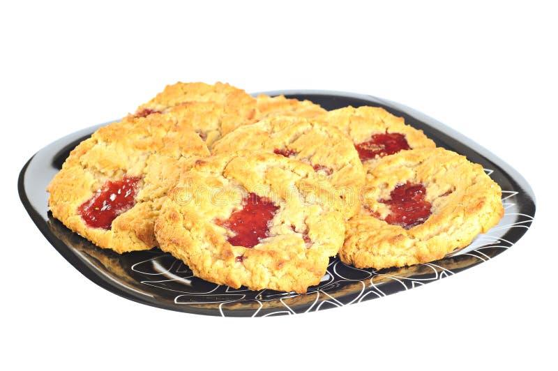 Biscuits délicieux avec de la confiture de fraise d'un plat, sur le fond blanc photographie stock