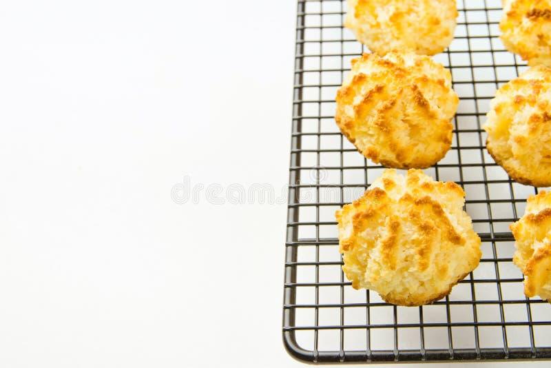 Biscuits délicieux faits maison de macarons de noix de coco avec la croûte d'or sur la table de cuisine blanche de refroidissemen photo libre de droits