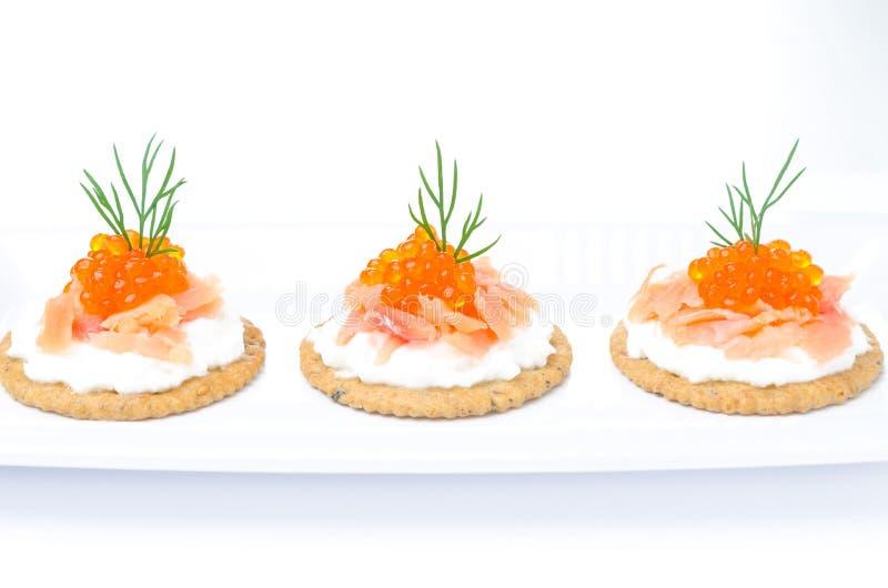 Biscuits d'apéritif avec le fromage fondu, saumon salé photographie stock libre de droits