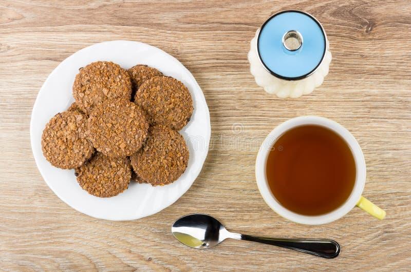 Biscuits de Brown dans le plat blanc, sucrier, tasse de thé image stock