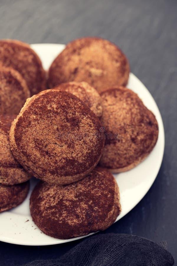 Biscuits de cannelle du plat blanc sur le fond en céramique noir image stock