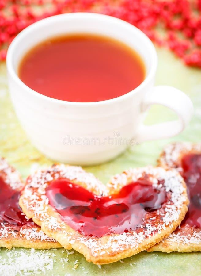 Biscuits de coeur avec la confiture et le thé photographie stock