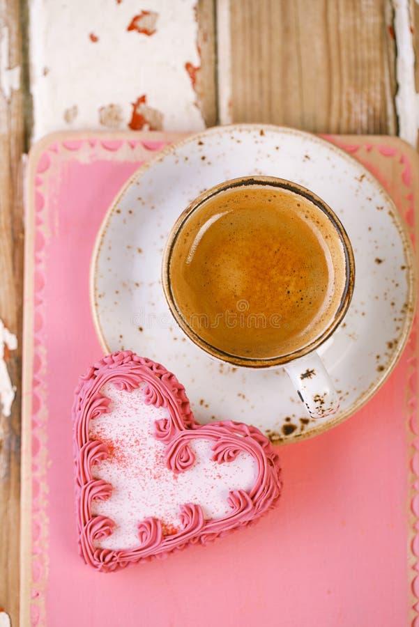 Biscuits de coeur et tasse de café rouges d'expresso sur la vieille table en bois photo stock