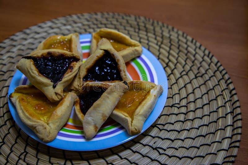 Biscuits de confiture de myrtille et d'abricot de Hamantash Purim dans le plat color? avec le fond en bois de table image libre de droits