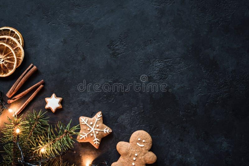 Biscuits de décorations, de pain d'épice de Noël, lumières de Noël et épices sur le fond foncé Moquerie de conception  photographie stock libre de droits